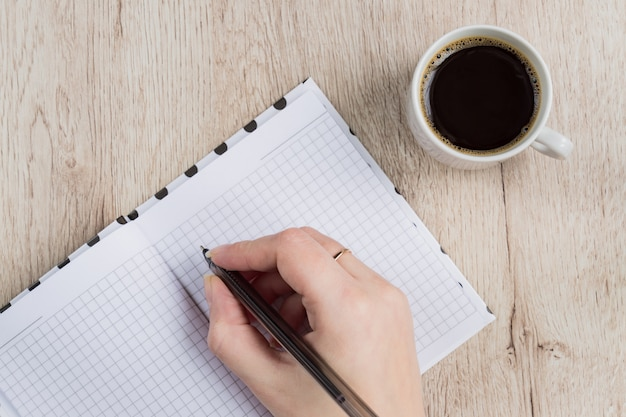 Young woman hand hold opened notebook pages with black pen next to cup of coffee on  wooden table. top view.