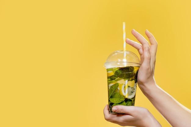 Молодая женщина рука стакан коктейля с мятой. студийное фото с желтым фоном.