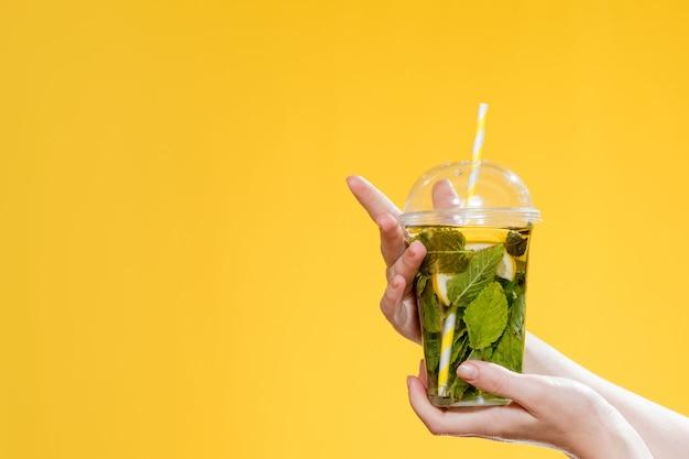 Молодая женщина рука стакан коктейля с мятой