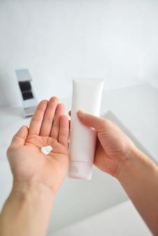 젊은여자가 손을 잡고 흰색 튜브를 표시 하 고 크림을 적용
