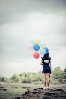 カラフルな風船を持つ若い女性の手