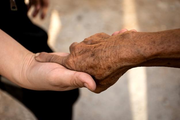 高齢者の手を握って若い女性の手。