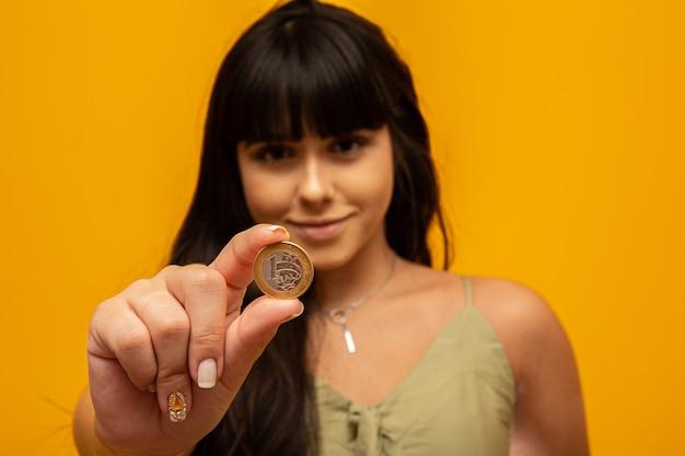 Рука молодой женщины держа одну реальную монетку концепции финансов бразилии.