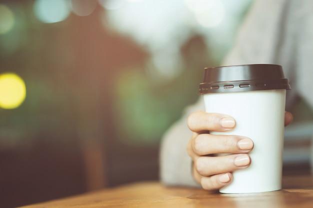 Молодая женщина рука бумажный стаканчик на вынос пить кофе горячий на деревянном столе в кафе кафе. x9