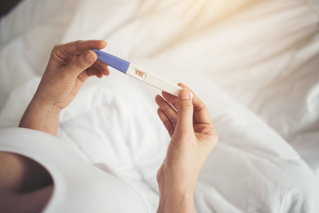 Young woman hand holding pregnancy test