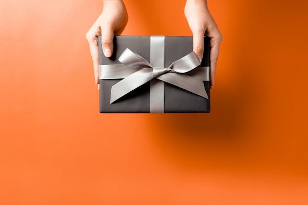 Рука молодой женщины с предложением подарочной коробки получателю