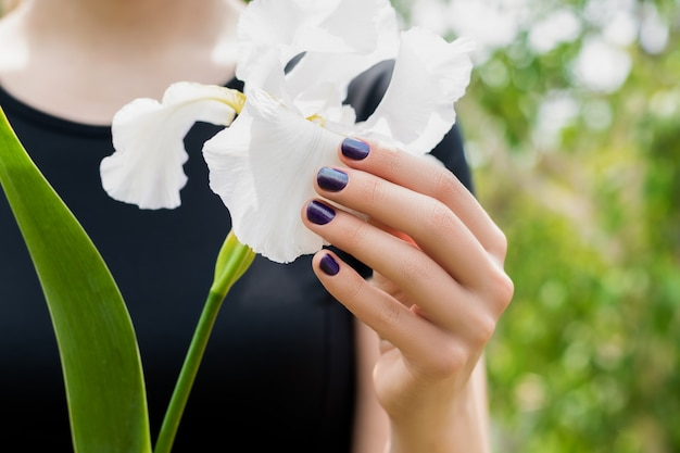 Young woman hand with beautiful purple nail art design holding white iris flower in spring garden