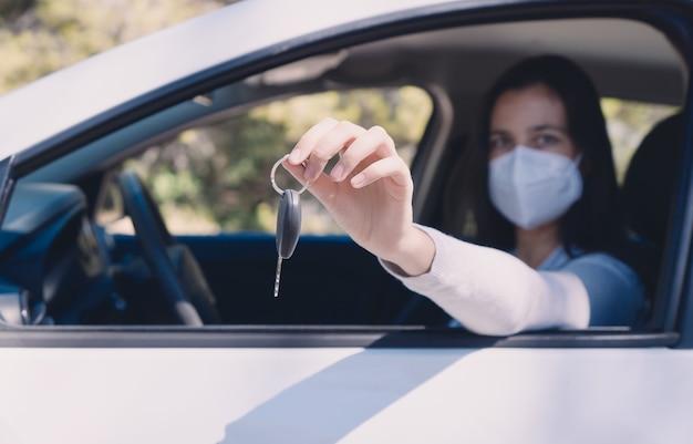 Молодая женщина передает ключи от машины в защитной маске во время пандемии covid-19