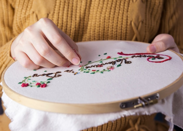 Young woman hands are embroidered happy valentines day