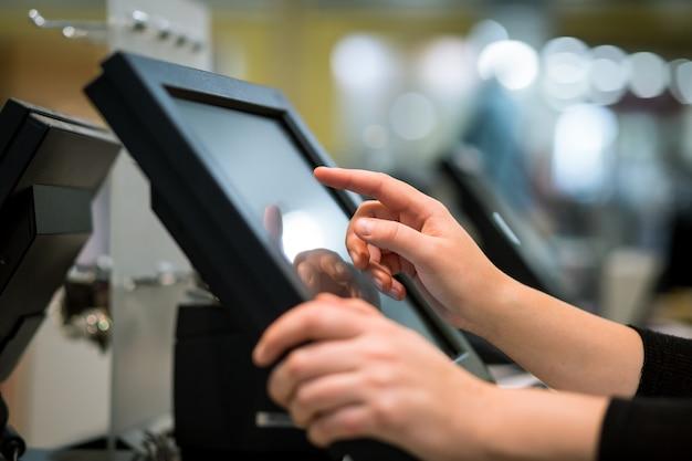 Молодая женщина считает руки, вводя скидку на кассовый аппарат с сенсорным экраном