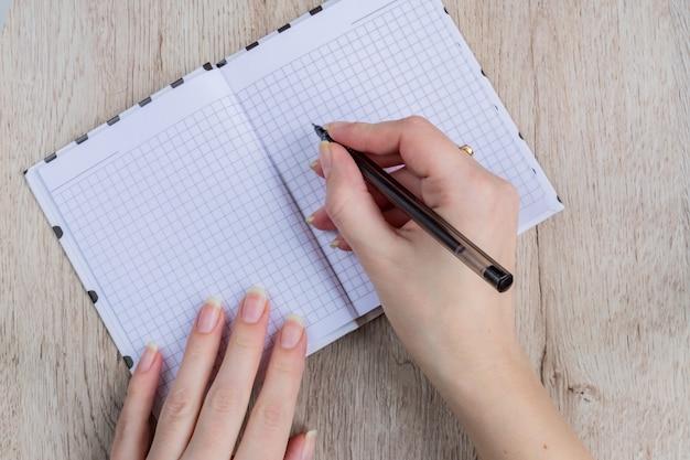 若い女性の手は、木製のテーブルに黒のペンで開いたノートページを保持します。