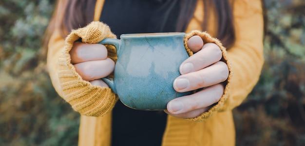 Молодая женщина в руках держит синюю кружку чая на открытом воздухе сезонной концепции