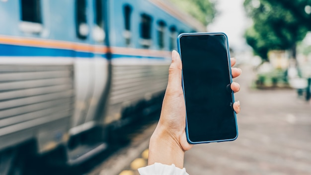 インターネットキャッシュレスによる予約と支払いのためにホテルの部屋を検索するために鉄道駅で携帯電話を持っている若い女性の手。