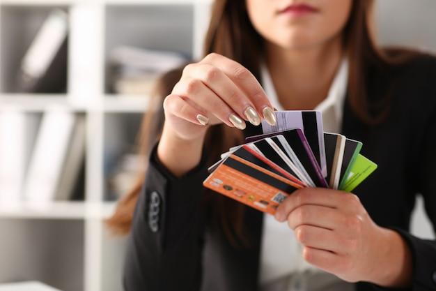 様々な銀行カードを保持している若い女性の手