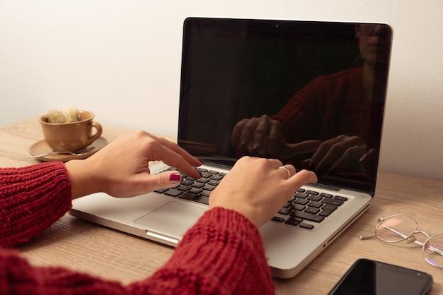 若い女性は、コンピューターの画面にコピースペースと明るい壁とオフィスの小道具と机の上のティーカップと木製のテーブルの上のラップトップキーボードを手渡します