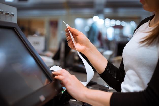 Молодая женщина вручает сканирование / ввод скидки / распродажи на квитанции, кассовый аппарат с сенсорным экраном, рынок / магазин