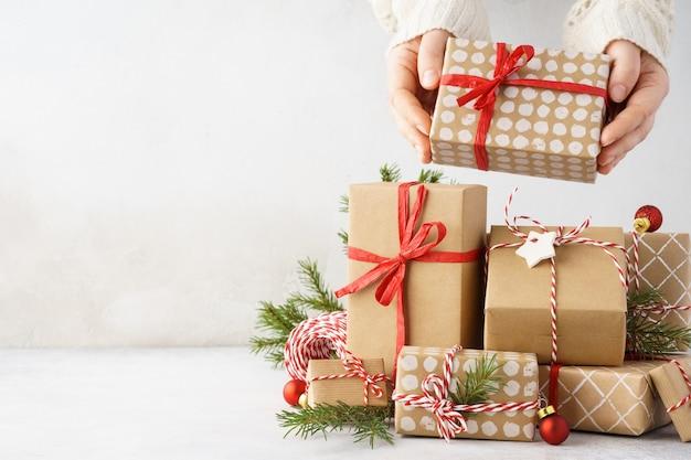 선물의 큰 스택에서 선물 상자를 복용하는 젊은 여자 손