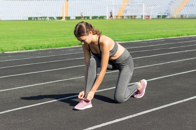 Young woman hands tie laces on her pink sport shoes on a stadium