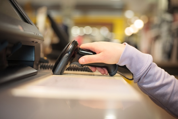 Young woman hands using scanner for scanning goods for a customer at huge shopping center