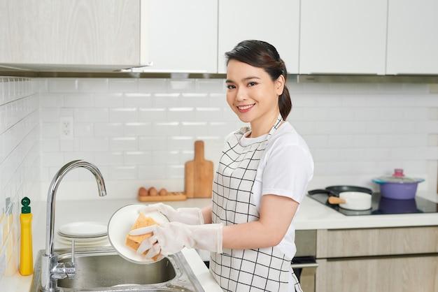 Молодая женщина с красивым маникюром моет посуду в раковине на кухне, используя губку с мыльной пеной