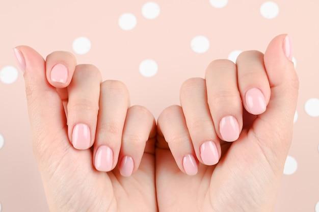 Руки молодой женщины со стильными модными ногтями, розовый маникюр на пастели с белыми блестками