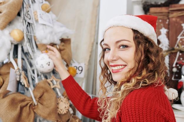 クリスマスツリーに安物の宝石をぶら下げ若い女性
