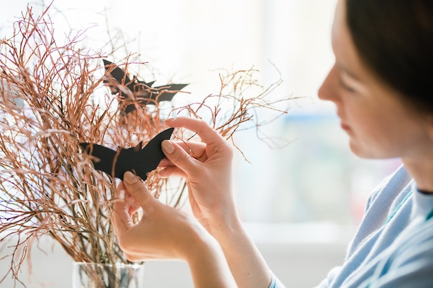 Young woman hanging black handmade bats on dry branches while preparing decorations for halloween