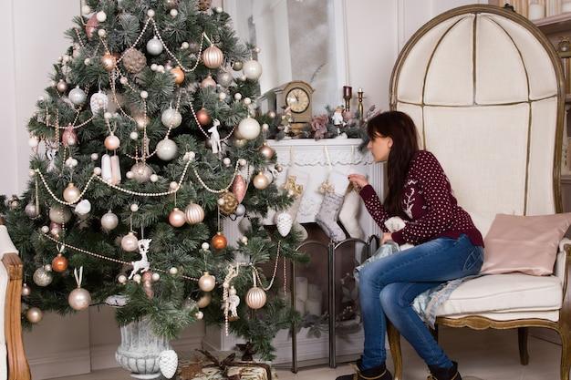 リビングルームのインテリアの大きな装飾されたクリスマスツリーと一緒に暖炉にクリスマスの靴下をぶら下げて若い女性