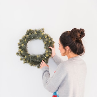 Young woman hanging christmas wreath