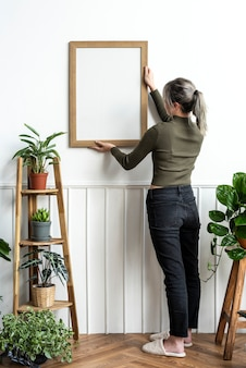 Young woman hanging a frame on the wall