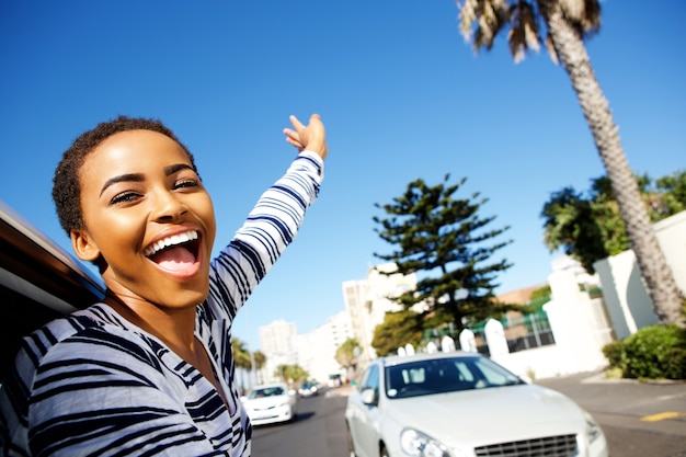 Young woman hanging outside car window with arms raised