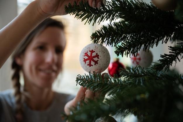 クリスマスツリーに赤と白の休日の安物の宝石をぶら下げて若い女性
