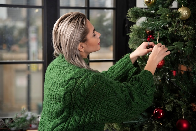 A young woman hangs a christmas tree toy on a branch of a fir tree