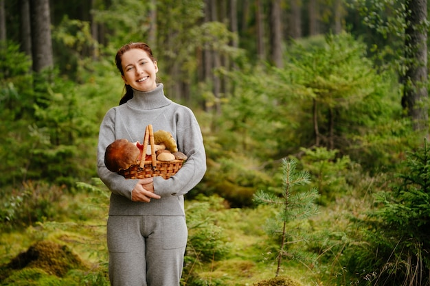 Young woman happily holds a wicker basket with edible mushrooms against the background of forest