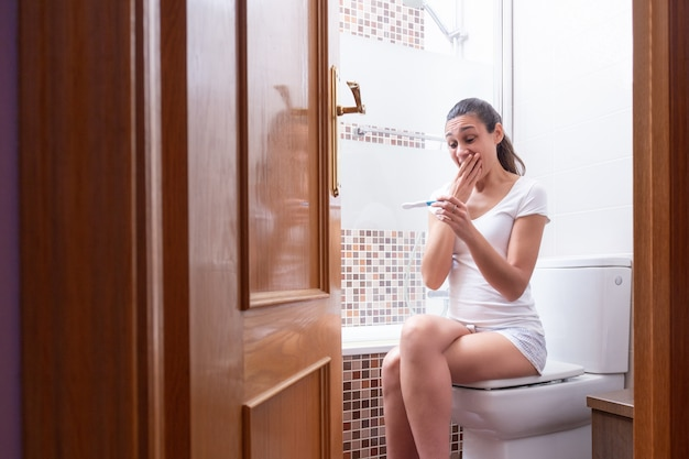 Young woman, happily looking at the pregnancy test in the bathroom at home