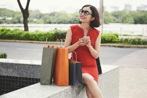 ショッピングの後の幸せな若い女性