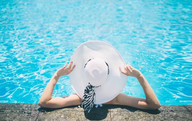 Молодая женщина счастлива в большой шляпе, отдыхая в бассейне, путешествия рядом с пляжем на закате. концепция лета