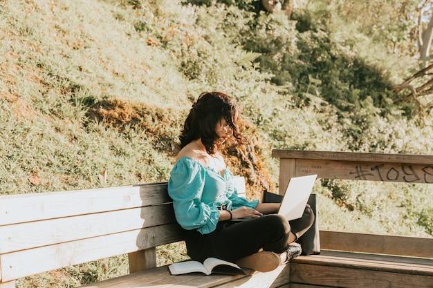 Молодая женщина счастлива, используя свой ноутбук в парке во время супер заката во время супер солнечного дня, работает на открытом воздухе