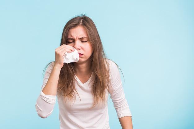 若い女性は青い壁に鼻水があります