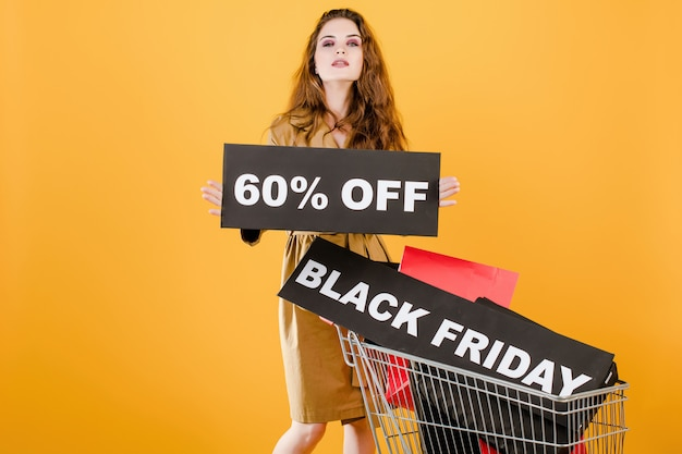 Young woman has black friday 60% off sign with cart full of shopping bags and signal tape isolated over yellow