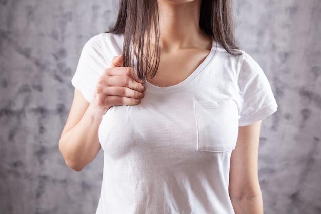 Молодая женщина болит в груди на сером