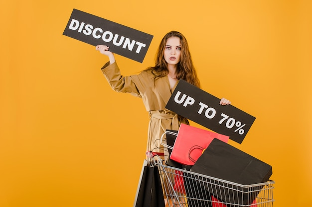 Young woman has discount up to 70% sign with cart full of shopping bags and signal tape isolated over yellow