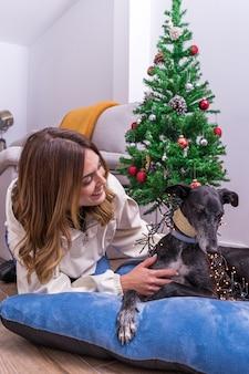 若い女性は彼女の犬と一緒にクリスマスツリーを飾ることを楽しんでいます。メリークリスマスと新年あけましておめでとうございますのコンセプト。幸せな休日。テキスト用のスペース