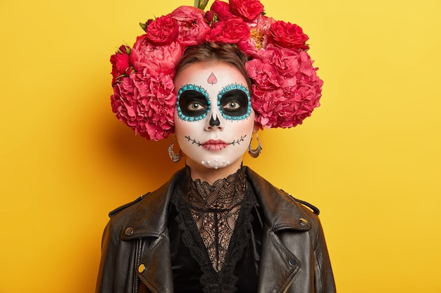Young woman has funky makeup and costume, wears wreath of red flowers, has traditional outlook for two day mexican holiday, solated on yellow