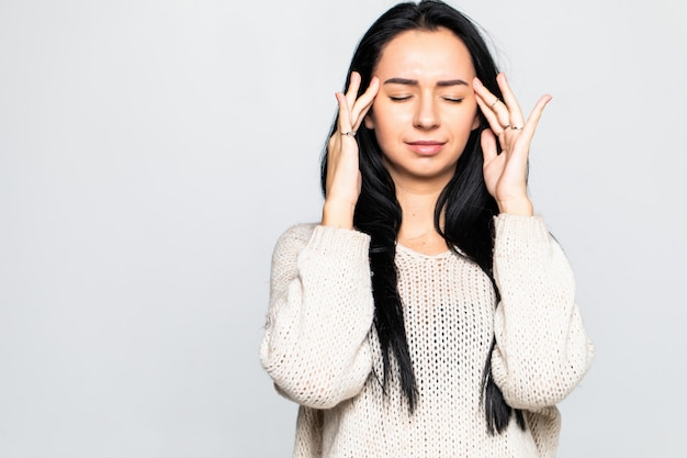 若い女性は灰色の壁に分離された頭痛