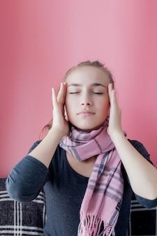 若い女性はピンクの背景に頭痛を持っています。