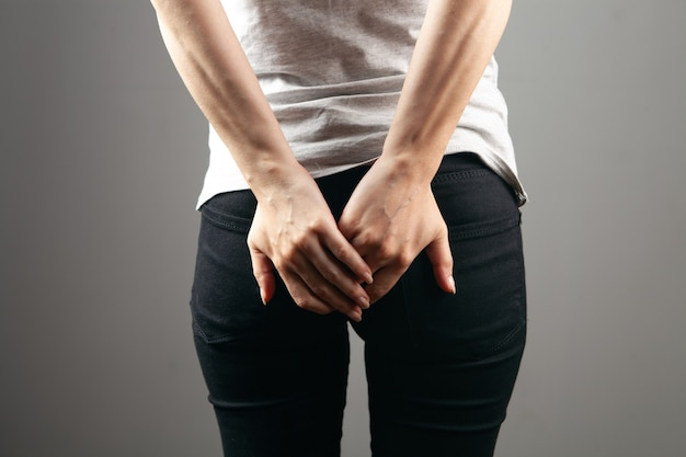 Young woman has hemorrhoids on gray background