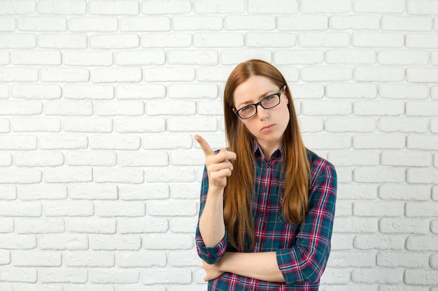 Young woman has idea, pointing with finger up