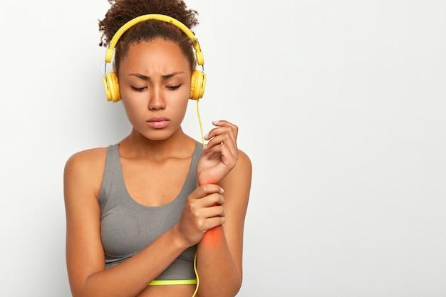 若い女性が手首を負傷し、赤い痛みの場所で腕に触れる