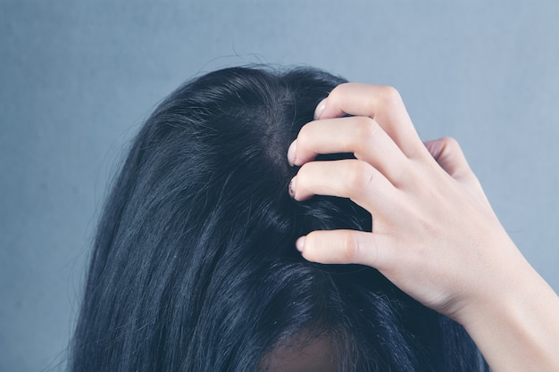 A young woman has an itchy head